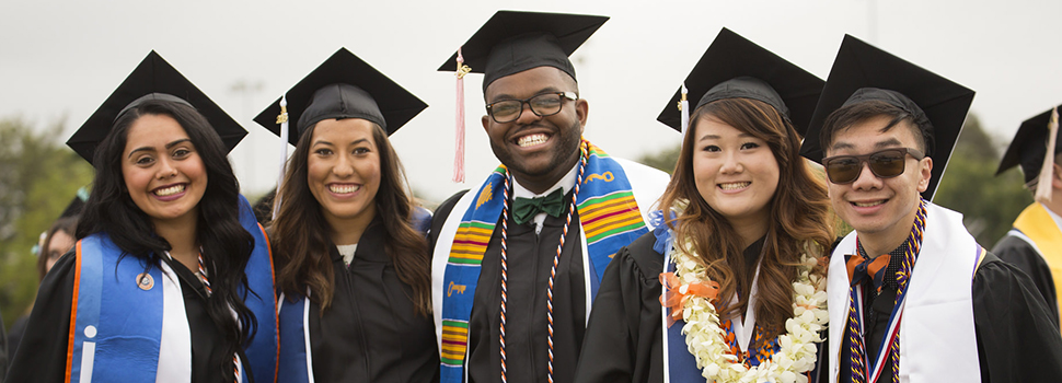 Students smiling for a picture on graduation day.